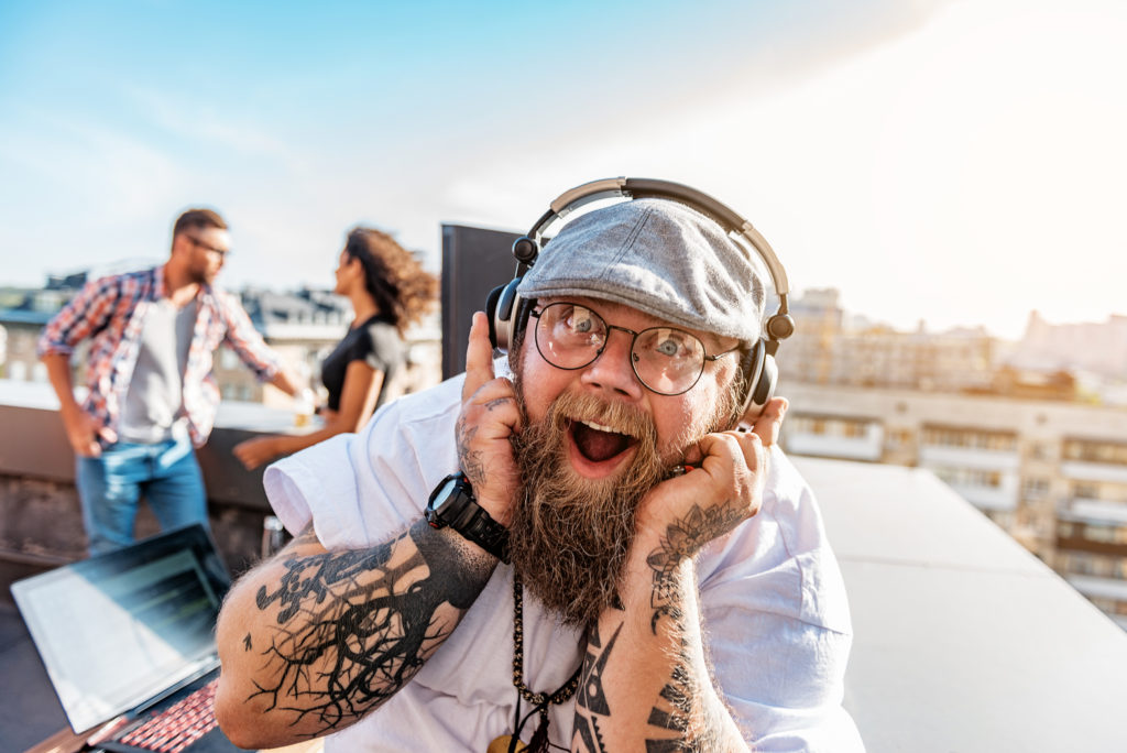 I am crazy about music. Happy fat bearded man is touching headphones and laughing. He is looking at camera with excitant while standing on roof on party. Portrait