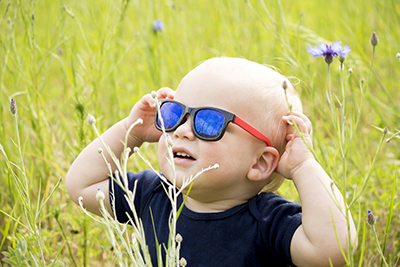 Funny baby boy in sunglasseslooking at sun in the field cornflowes.