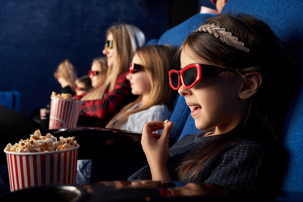 Children sitting in movie theatre, watching film or cartoon, wearing in 3d glasses. Cheerful little girl eating popcorn, holding popcorn bucket.