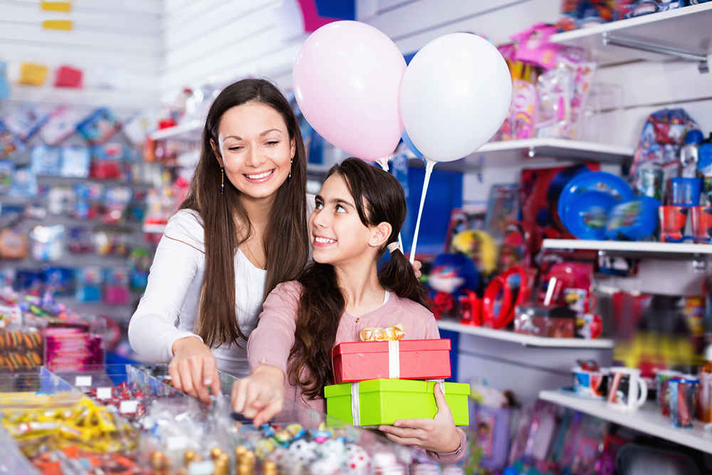 Smiling happy cheerful female and girl with gifts and balloons in the candy store